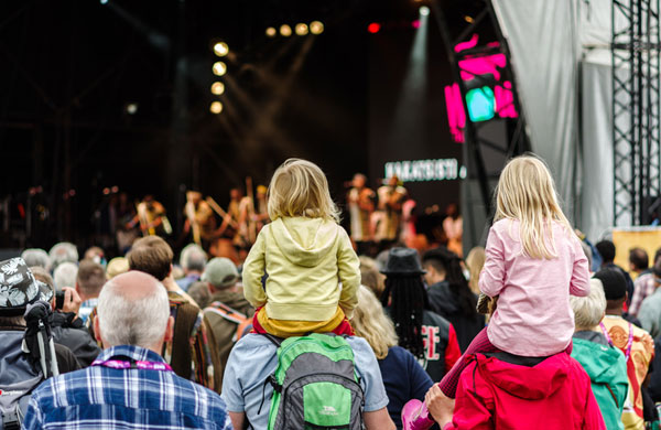 children sitting on shoulders at festival