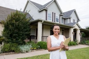 realtor holding a clipboard in front of a residential home