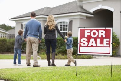 a famliy facing away in front of the house with for sale signage on the side